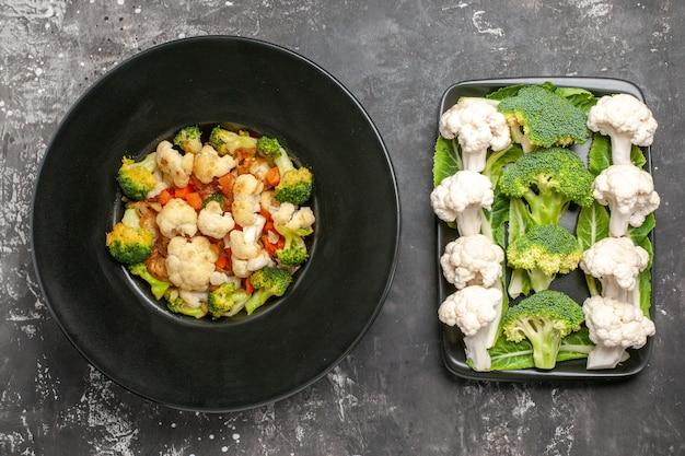 Top view broccoli and cauliflower salad on black oval plate raw broccoli and cauliflower on black rectangular plate on dark surface