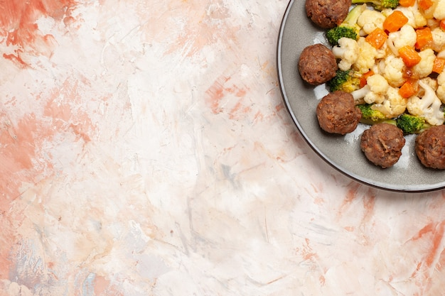 Top view broccoli and cauliflower salad and meatball on plate on nude isolated surface with copy space