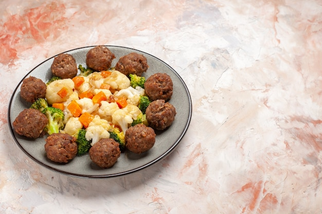 Top view broccoli and cauliflower salad and meatball on plate on nude isolated surface with free space