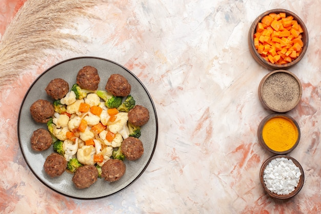 Top view broccoli and cauliflower salad and meatball on plate vertical row bowls with different spices on nude surface with free space