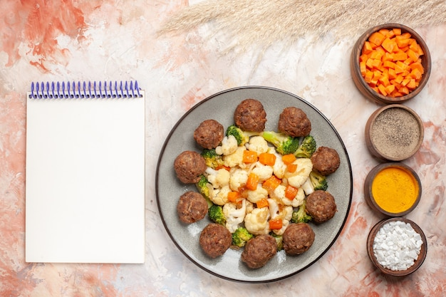 Top view broccoli and cauliflower salad and meatball on white plate vertical row bowls with different spices a notepad on nude surface