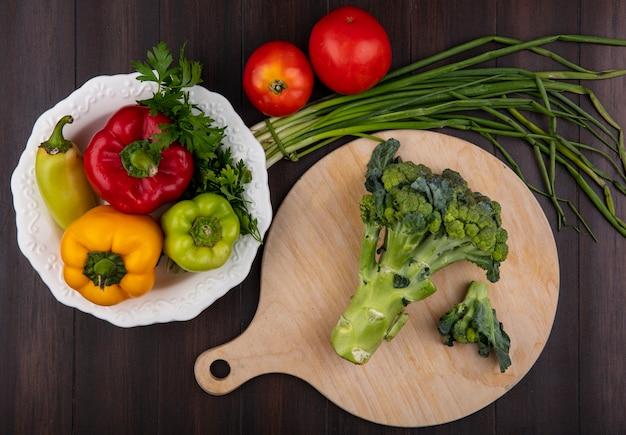 Vista dall'alto broccoli su un tagliere con peperoni su un piatto e cipolle verdi con pomodori su uno sfondo di legno