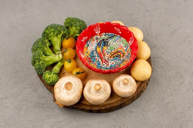 Vista dall'alto funghi broccoli pomodori freschi maturi sulla scrivania marrone e piano chiaro