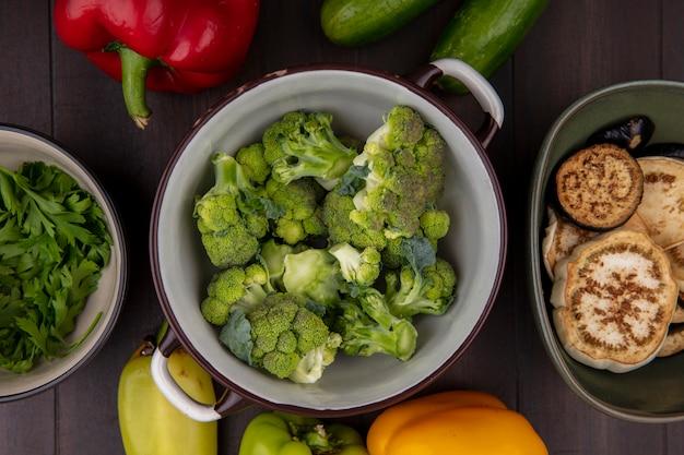Vista dall'alto broccoli in una casseruola con prezzemolo in una ciotola con e cetrioli su sfondo di legno Foto Gratuite