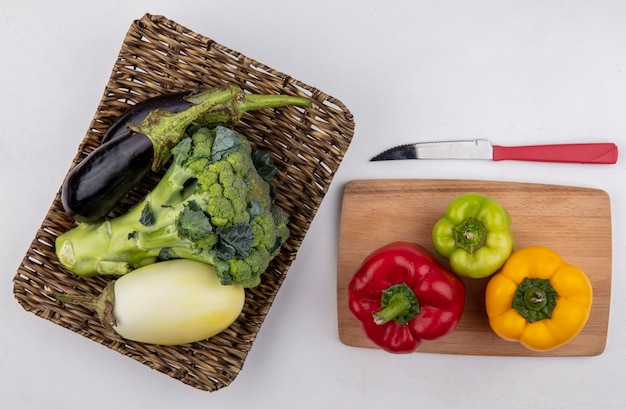Top view broccoli with black and white eggplants on a stand with colored bell pepper on a cutting board and a knife  on a white background