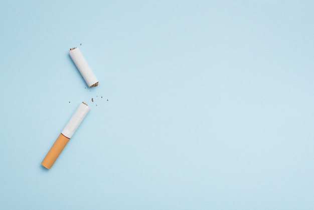 Top view of broken cigarette on blue background