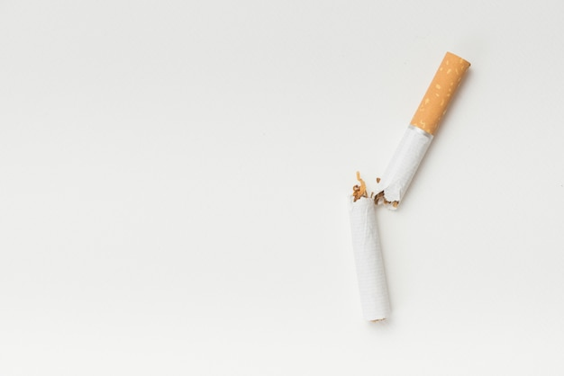 Top view of broken cigarette on white background