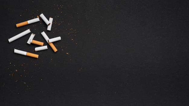 Top view of broken cigarette with tobacco on black backdrop