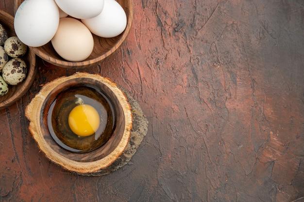 Vista dall'alto uovo crudo rotto all'interno del piatto con pollo e uova di quaglia