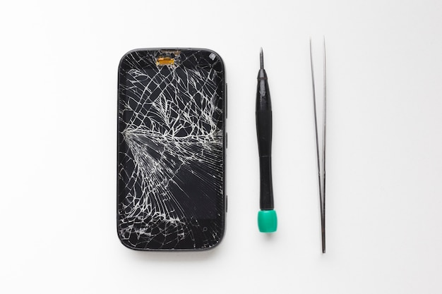 Top view broken smartphone with repair tools