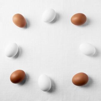 Вид сверху коричневые и белые яйца на столе