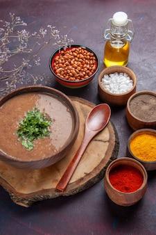 Vista dall'alto zuppa di fagioli marroni deliziosa zuppa cotta con diversi condimenti sulla superficie scura cena zuppa di fagioli colore pasto piccante