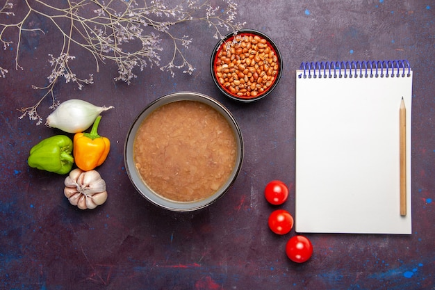 Top view brown bean soup with vegetables on dark desk vegetable soup meal food oil