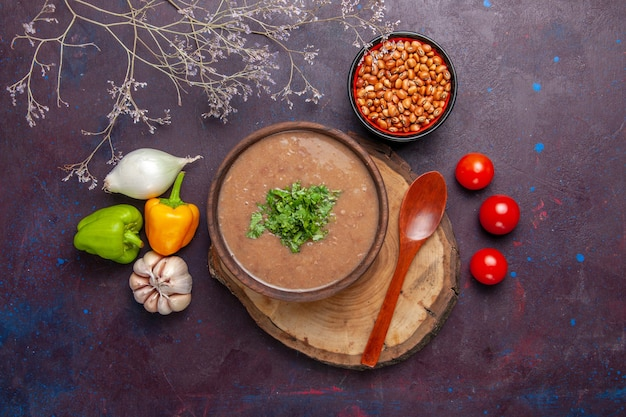 Top view brown bean soup with vegetables and greens on dark surface vegetable soup meal food oil