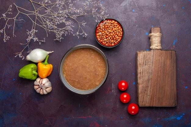 上面図暗い表面に野菜が入った茶色の豆のスープ野菜スープミールフードオイル