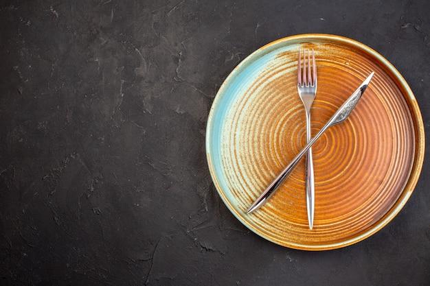 어두운 표면에 접시 포크와 나이프와 상위 뷰 갈색 큰 트레이