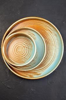 Vista dall'alto vassoio grande marrone con piatto dello stesso colore su superficie scura