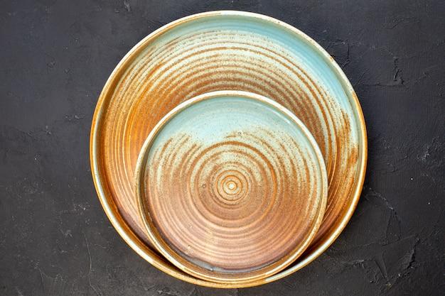 Вид сверху коричневый большой поднос с тарелкой того же цвета на темной поверхности