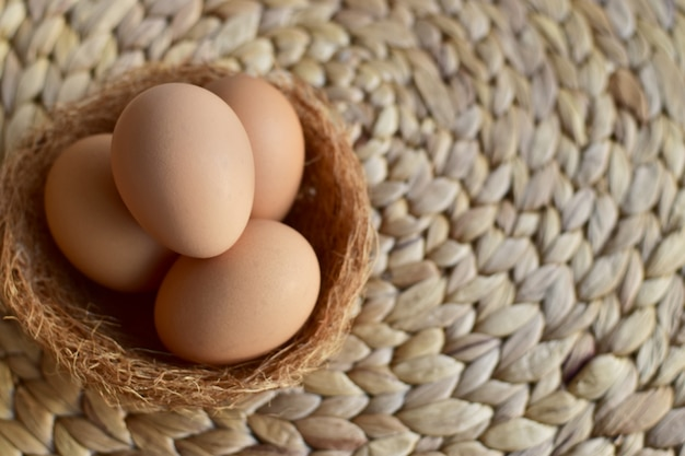 Top view of brown chicken/hen eggs in a nest on top of a natural mat