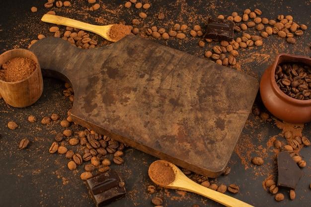 Una vista dall'alto di semi di caffè marroni con barrette di cioccolato su tutto il tavolo marrone