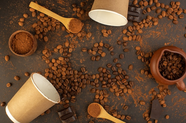 A top view brown coffee seeds with choco bars and coffee cups