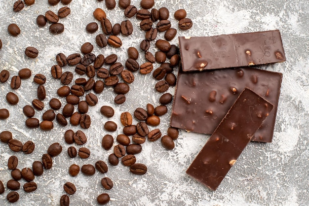 Top view of brown coffee seeds with chocolate bars on a white surface