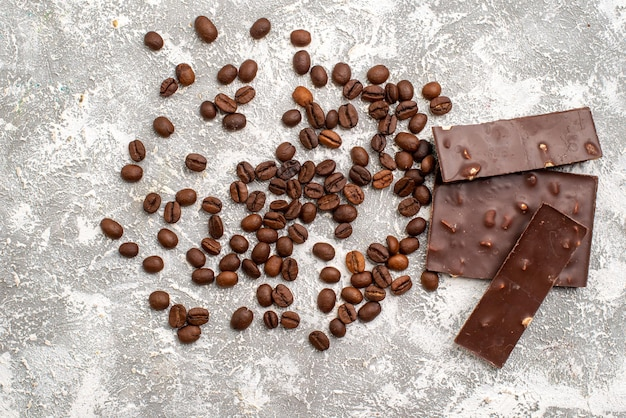 Top view of brown coffee seeds with chocolate bars on white surface