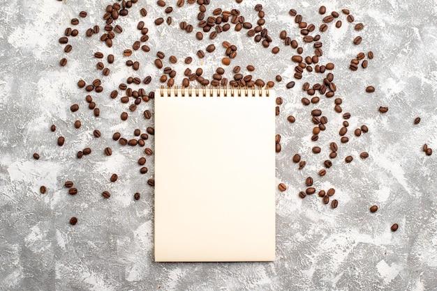 Vista dall'alto di semi di caffè marrone con blocco note sulla superficie bianca