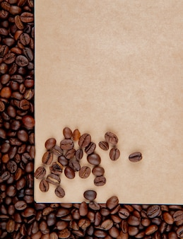 Top view of brown craft paper sheet on coffee beans background