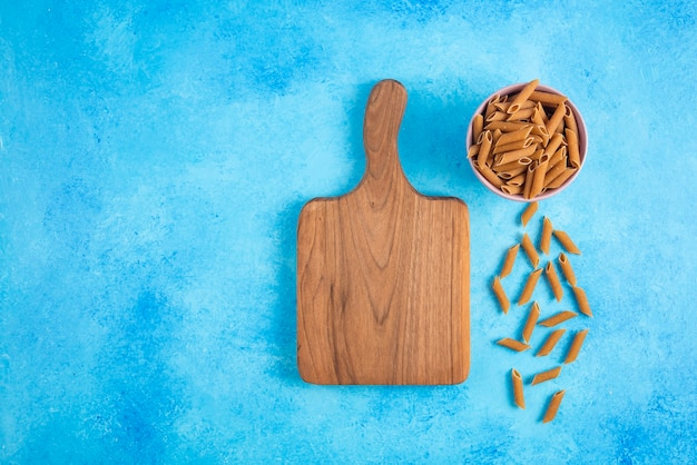 Top view of brown dietic past a and wooden chopping board on blue background.