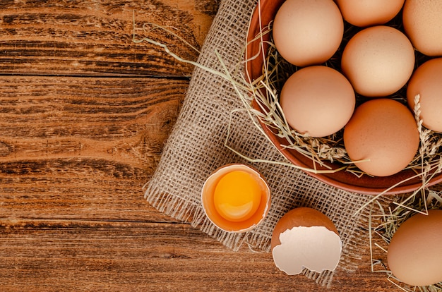 Top view of brown eggs in bowl and broken egg with yolk on wooden table