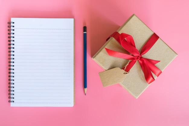 Вид сверху коричневый подарочной коробке и записной книжке на розовый пастельный цвет фона.
