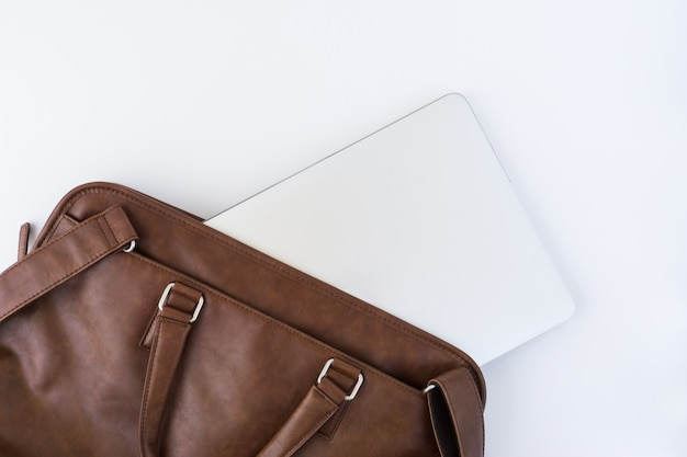 Top view of brown handbag with tablet