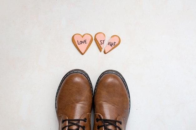 Top view of brown leather boots and two broken heart gingerbread cookies decorated with pink glaze with the message love stinks on the floor. heartbreak concept.
