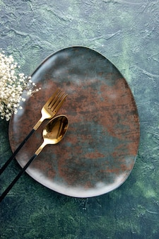 어두운 표면에 황금 숟가락과 포크와 상위 뷰 갈색 접시 음식 색상 레스토랑 주방기구 저녁 식사 칼