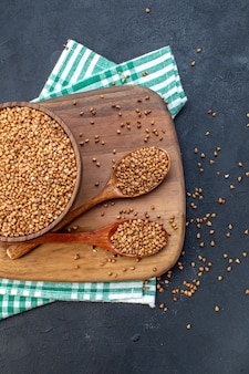 Top view brown raw buckwheat inside plate on dark background color food seed health fresh plant lentil meal