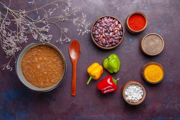 Vista dall'alto zuppa marrone all'interno del piatto con fagioli e condimenti sulla superficie scura zuppa di verdure farina alimentare olio da cucina