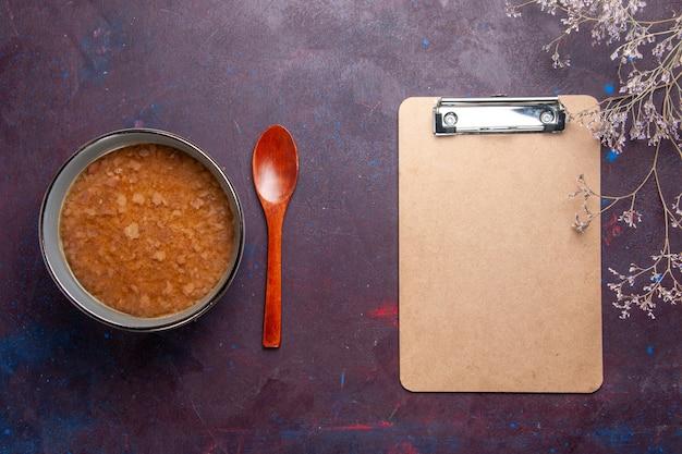 暗い表面のスープ野菜ミール食品キッチンオイルにメモ帳が付いているプレートの内側の上面図茶色のスープ
