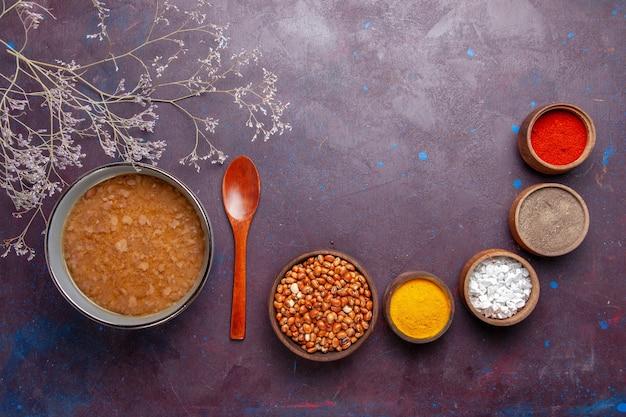 Vista dall'alto zuppa marrone con diversi condimenti sulla superficie scura zuppa di verdure farina alimentare olio da cucina