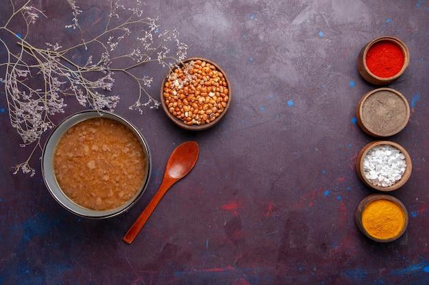 Vista dall'alto zuppa marrone con diversi condimenti sulla superficie scura zuppa di verdure pasto cibo olio da cucina