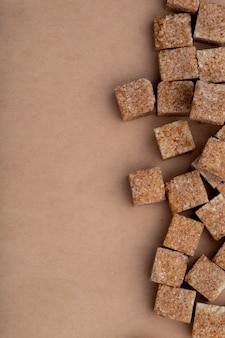 Top view of brown sugar cubes arranged on brown paper texture background with copy space