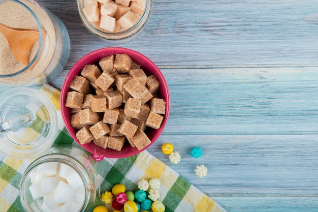 Top view of brown sugar cubes in a pink bowl and various types of sugar in glass jars on rustic background with copy space