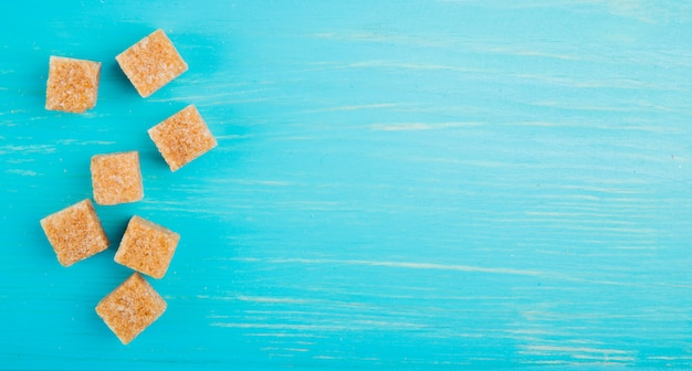 Top view of brown sugar cubes scattered on blue wooden background with copy space