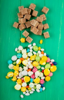 Top view of brown sugar cubes with various colorful sugar candies on green wooden background