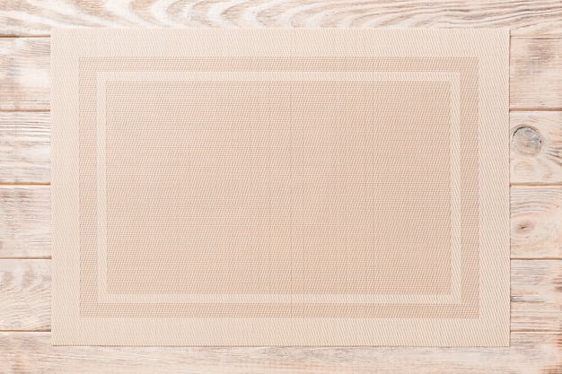 Top view of brown tablecloth for food on wooden.