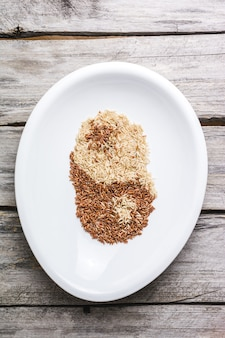 Top view of brown and white grains mixed in a white plate creating ying and yang
