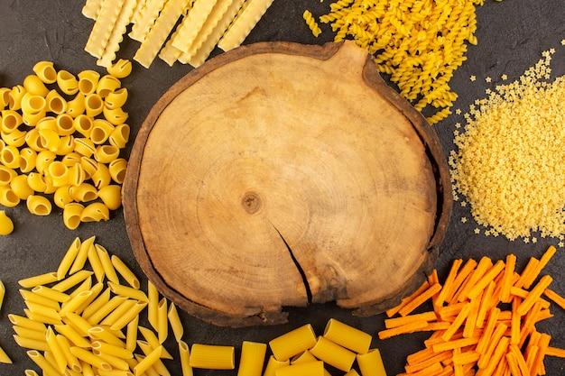 A top view brown wooden desk along with different formed yellow raw pasta isolated on the dark