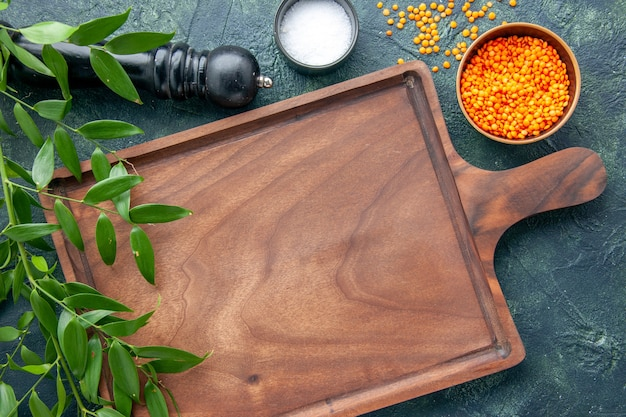 ダークブルーの背景に茶色の木製デスクの上面図古代料理色肉包丁食品