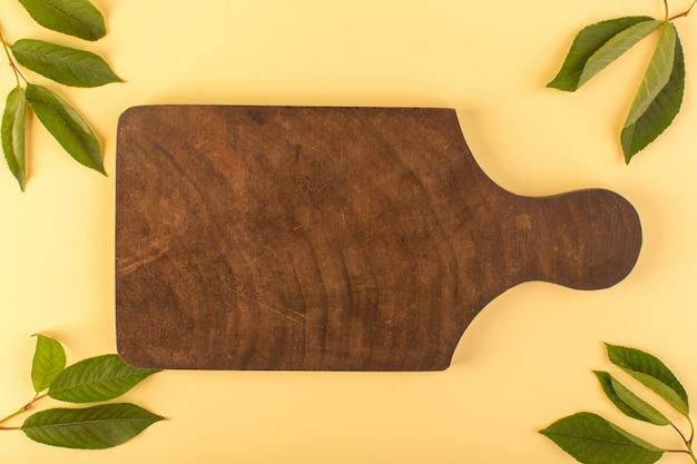 Uno scrittorio di legno marrone di vista superiore rustico insieme all'albicocca delle foglie verdi colorata