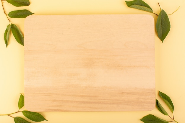 A top view brown wooden desk rustic along with green leaves apricot colored